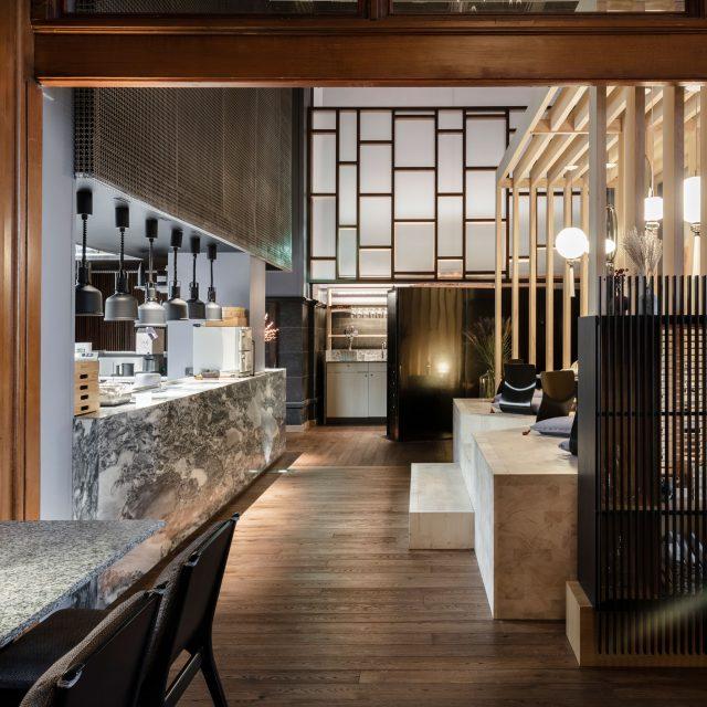 Vrå interiör japansk sittning med utsikt över kök i sten och trä